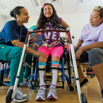 Determined, Stephanie Gonzalez tries standing on her own with her mother's and therapist's encouragement. Family involvement is a critical part of preparing for discharge and continuing the progress at home.